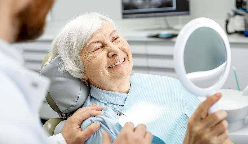 happy-old-patient-with-dental-implants-800x466